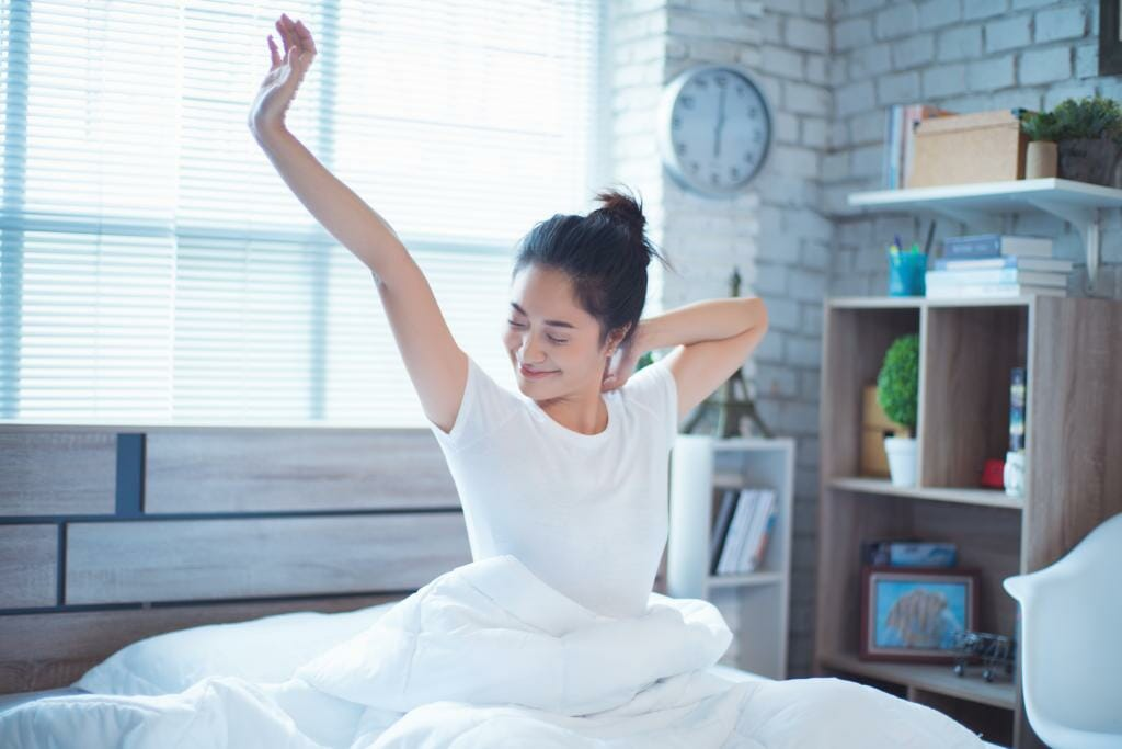 Woman stretching after waking up in bed