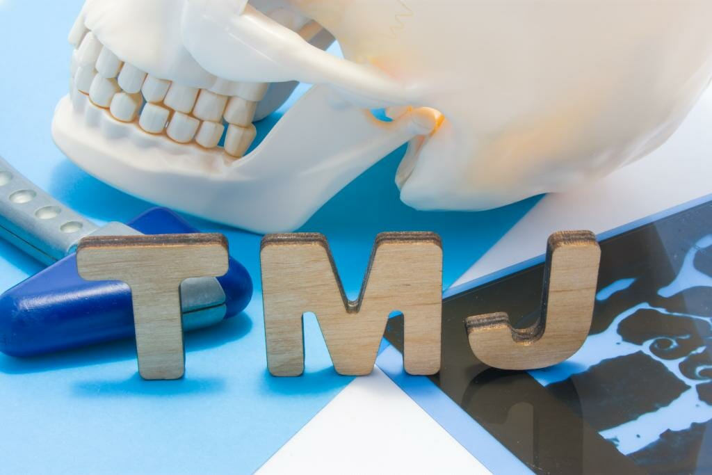 Closeup of jaw with block letters T, M, and J