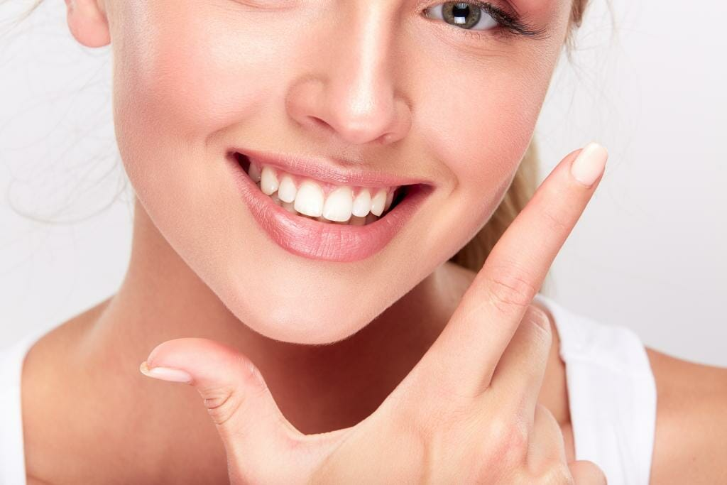 Smiling woman framing her jaw with thumb and pointer finger