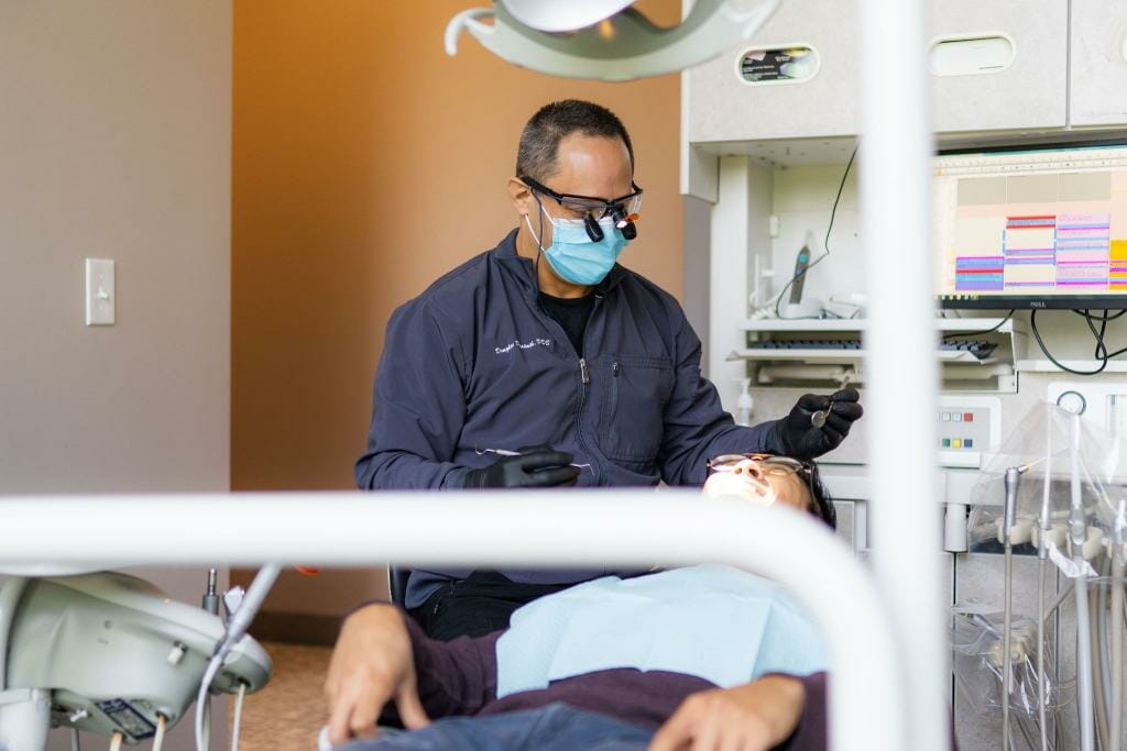 Dr. Desatnik examining patient's teeth